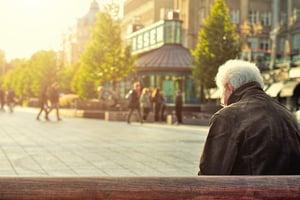 retired man on benchin city square
