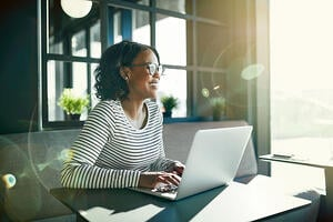 woman smiling and workign on laptop