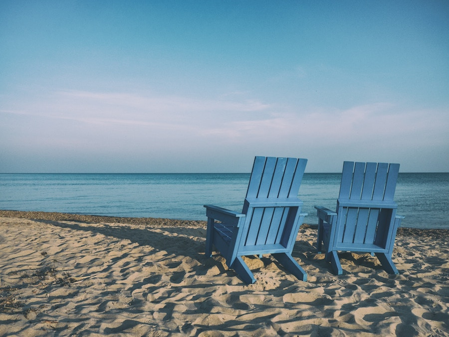 blue chairs on beach ocean sky sand
